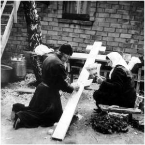 Монах у креста, старушка читает газету