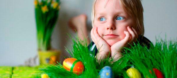 Ребенок в траве с пасхальными яйцами