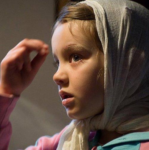 Девочка совершает крестное знамение