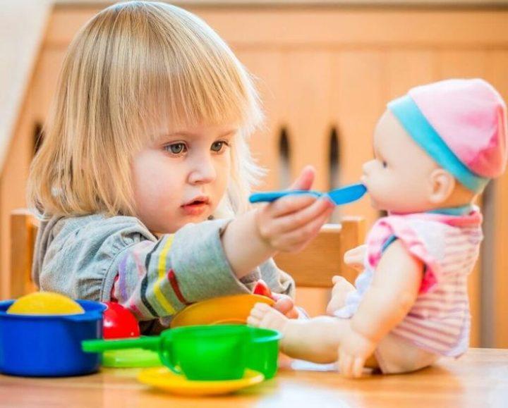 Игры с детьми. Девочка кормит куклу